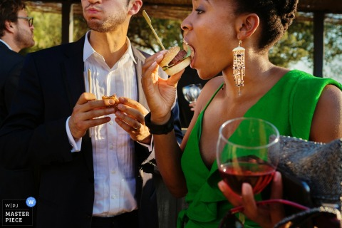 Two guests eat sliders and drink wine outside during the reception in this photo by a Madrid, Spain wedding photographer.