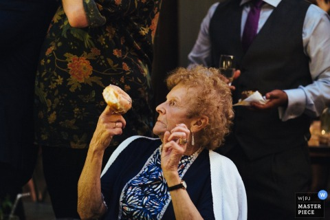 A woman holds a doughnut on her finger in this photo by a London, England wedding reportage photographer.