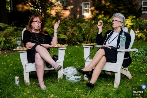 Two women sit outside eating food together in this photo by a Washington, D.C. wedding photographer.