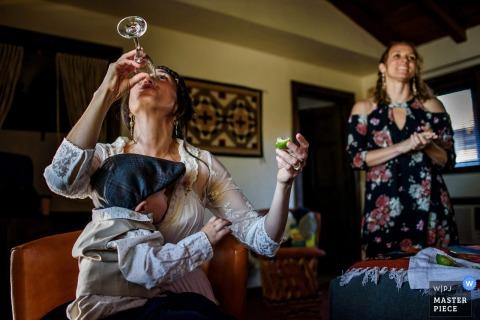 Une femme termine son verre alors qu'un petit garçon est assis sur ses genoux sur cette photo réalisée par un photographe de mariage de San Diego, en Californie.