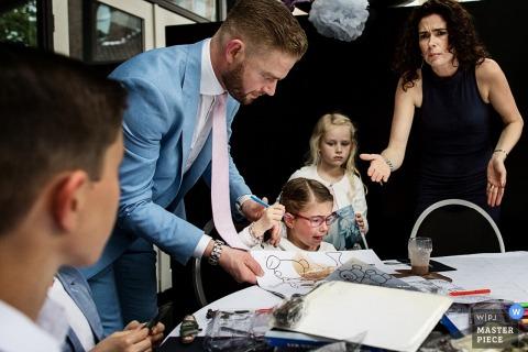 Ein junges Mädchen ärgert sich, als ein Mann ihr Malbuch aufnimmt, nachdem ein niederländischer Hochzeitsfotograf dieses Foto verschüttet hat.