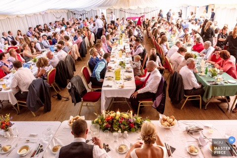 The bride and groom sit in front of guests seated at long tables during the reception in this photo by a Waterford, Munster wedding photographer.