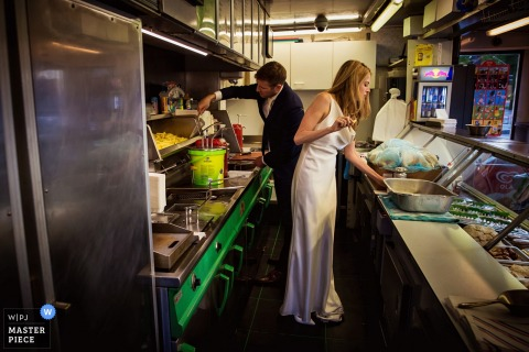 The bride and groom work in a kitchen in their wedding clothes in this photo by a Holland, Netherlands wedding photographer.