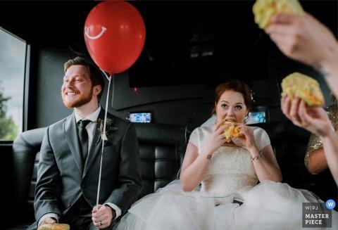 De bruid en andere gasten eten terwijl de bruidegom een rode ballon vasthoudt op deze foto door een trouwfotograaf uit British Columbia, Canada.