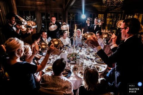 Foto van servers die tegelijkertijd de stola's van het voedsel van de gasten optillen door een huwelijksfotograaf van Leon.
