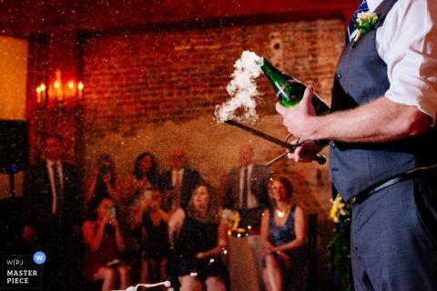 Foto de un hombre que usa una espada para descorchar una botella de champaña de un fotógrafo de bodas de Birmingham, AL.