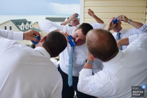 Foto des shotgunning Bieres einiger Männer durch äußere Banken, NC-Hochzeitsfotograf.