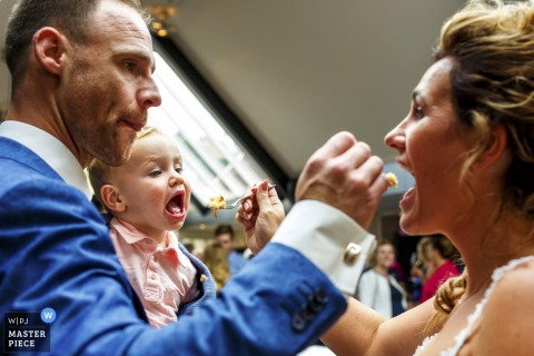 Photo of the groom feeding the bride a bite of cake as she feeds a little boy a bite by a Netherlands wedding photographer.