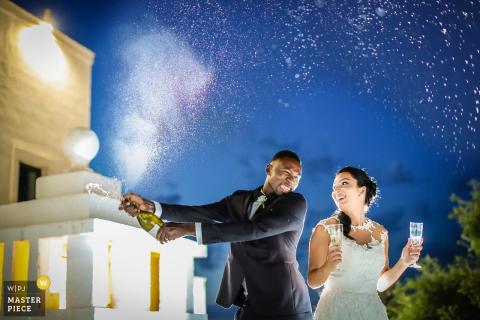 Foto der Braut und des Bräutigams draußen nachts mit der Braut, die zwei Gläser hält, während der Bräutigam eine Flasche Champagner von einem Apulien-Hochzeitsfotografen öffnet.