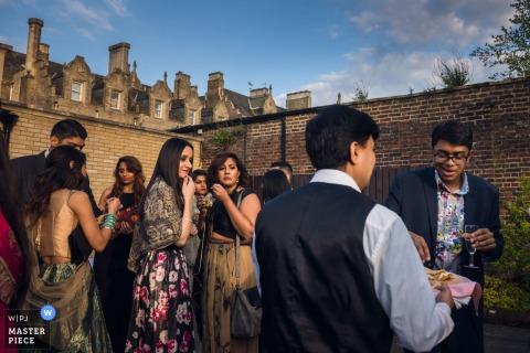 Hochzeitsempfangfoto Londons, England von den Gästen, die miteinander sprechen, während ein Butler Getränke vertreibt