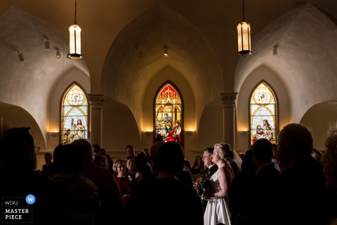 The bride walks down the aisle surrounded by guests in a church with stained glass windows in this photo by a Madison, WI wedding photographer.