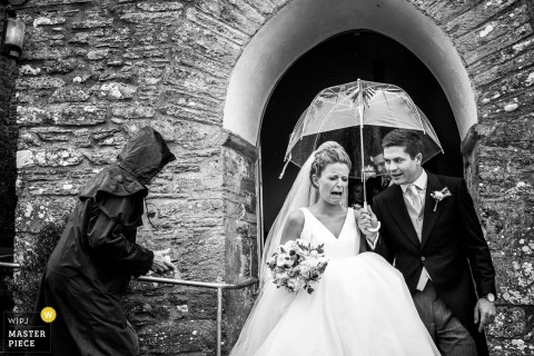 The groom holds an umbrella over himself and the bride as she cries exiting the ceremony in this black and white photo by a Devon, England wedding reportage photographer.