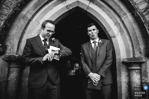Twee mannen staan te wachten als men zijn horloge controleert voor de ceremonie in deze zwart-witfoto door een fotograaf van de huwelijksreportage van Devon, Engeland.