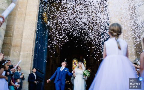 Guests fire confetti cannons as the bride and groom exit the ceremony in this photo by a France wedding photographer.