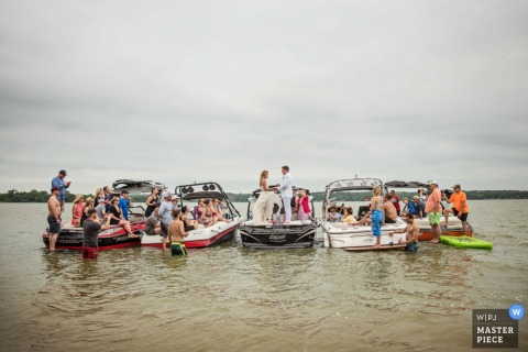 The bride and groom stand on the back of one boat as the guests sit in four others in this photo by a Baltimore, MD wedding photographer.