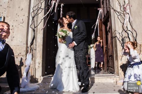 Die Braut und der Bräutigam küssen sich nach der Zeremonie, während die Gäste auf diesem Foto eines kalabresischen Hochzeitsfotografen Blütenblätter werfen.