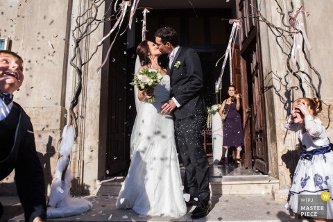 The bride and groom kiss after the ceremony as guests throw flower petals in this photo by a Calabria wedding photographer.