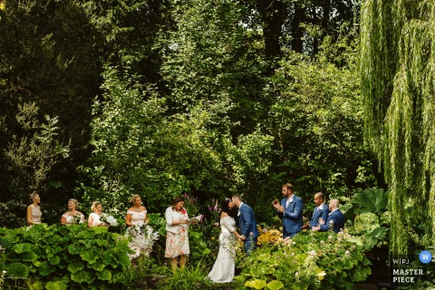 The bride and groom kiss during the ceremony surrounded by greenery in this photo by a Greater Manchester, England wedding reportage photographer.