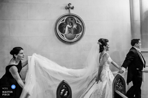 A woman helps the bride with her train as she walks down the aisle in this black and white photo by a Chicago, IL wedding photographer.