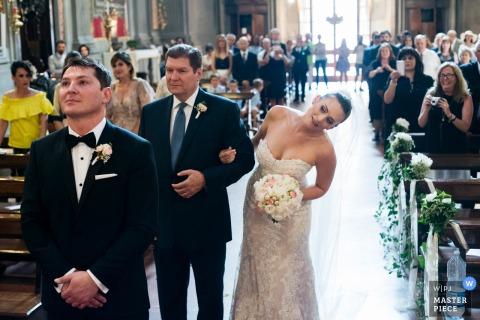 La novia se inclina para mirar al novio mientras sostiene el brazo de su padre en esta foto de un fotógrafo de bodas de Roma.