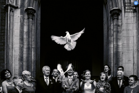 Les mariés remettent deux colombes après la cérémonie sur cette photo en noir et blanc réalisée par un photographe de mariage de Flandre orientale.