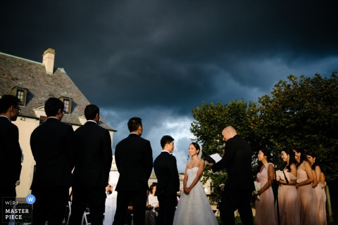 Photo of the bride and groom during the ceremony beneath a stormy sky by a Manhattan, NY wedding photographer.