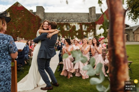 Photo of the bride and groom hugging at the end of the outdoor ceremony by a Dublin wedding reportage photographer.