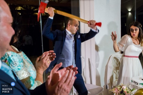 Guests clap and the bride fakes surprise as the groom pretends to cut the cake with an ax in this photo by an Alicante, Valencia wedding photographer.