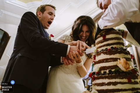The bride and groom make their first slice into the wedding cake in this photo by a Westphalia, Germany wedding photographer.
