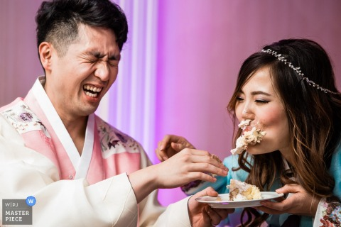 The groom laughs after shoving a piece of cake in the bride's face in this photo by an Atlantic City, NJ wedding photographer.