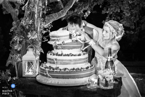 The bride shoves the groom's face into the wedding cake in this black and white photo by a Tuscany wedding photographer.