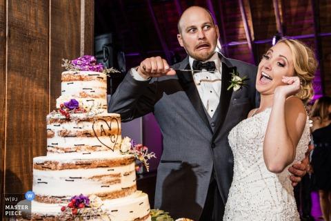 Le marié pointe en plaisantant un couteau sur la mariée alors qu'elle se prépare à couper le gâteau sur cette photo par un photographe de mariage du New Jersey.