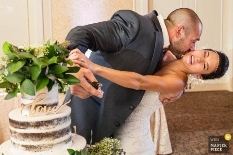 El novio besa a la novia en la mejilla mientras sostiene un pedazo de pastel en su mano en esta foto de un fotógrafo de bodas de Nueva Jersey.