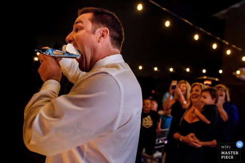 The groom eats a large piece of cake in one bite in this photo by a San Diego, CA wedding photographer.