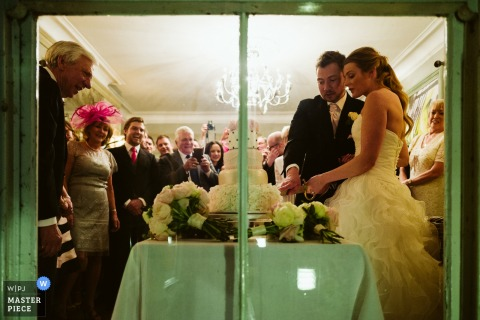 Photo of the bride and groom cutting their wedding cake, taken from outside by a Greater Manchester, England wedding reportage photographer.