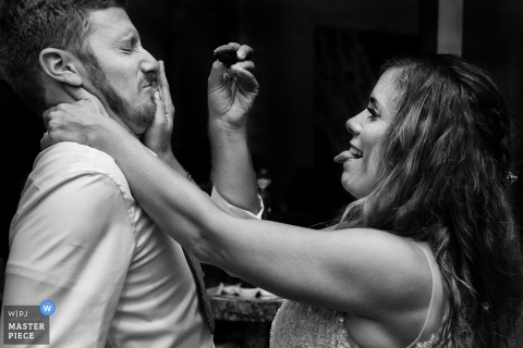 The groom makes a face as the groom shoves a piece of cake into his mouth in this black and white photo by a Carson City, NV wedding photographer.