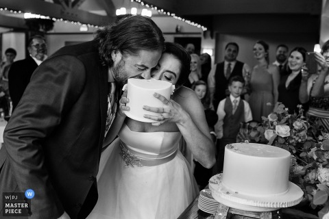 The bride holds up a tier of the wedding cake for her and the bride to eat in this black and white photo by a Carson City, NV wedding photographer.