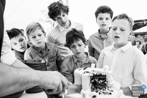 Children surround the wedding cake waiting for a slice in this black and white photo by an Antwerpen wedding photographer.