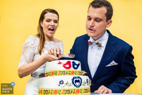 Photo of the bride and groom concentrating on cutting their wedding cake by a Prague, Czech Republic wedding photographer.