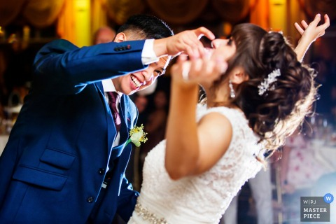 Photo of the groom feeding the bride a piece of cake by a New Jersey wedding photographer.
