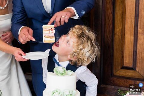 Foto van de bruidegom die een volledige plak van cake voedt aan een jonge jongen door een het huwelijksfotograaf van Holland.