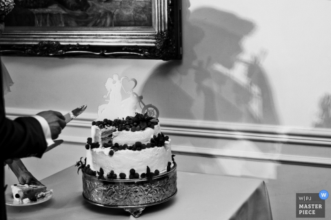 Black and white photo of the wedding cake with the shadow of the bride visible on the wall by a Krakow wedding photographer.