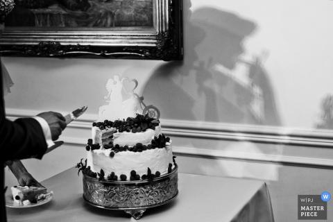 Photo noir et blanc du gâteau de mariage avec l'ombre de la mariée visible sur le mur par un photographe de mariage de Cracovie.