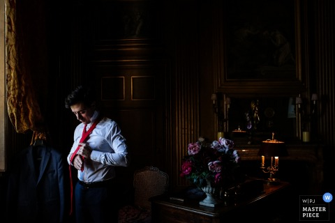 The groom puts on a red tie as he gets ready for the ceremony in this photo by a Lyon wedding photographer.
