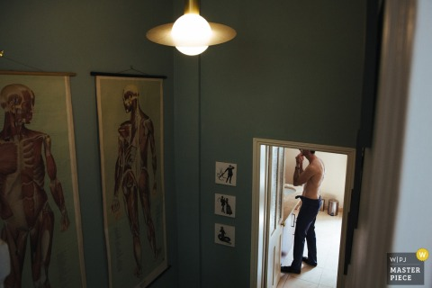 The groom gets ready in his room with large, anatomical drawings hanging in the hallway outside in this photo by a London, England wedding reportage photographer.