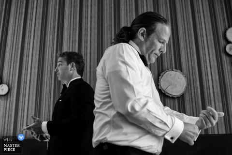 Two men stand facing opposite directions as they put on their cufflinks in this black and white photo by a Lake Tahoe, CA wedding photographer.