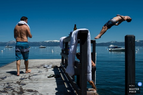 A man jumps backward off a dock into a lake in this photo by a Lake Tahoe, CA wedding photographer.
