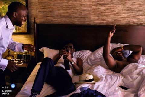 Deux hommes se détendent dans un lit tandis qu'un autre se prépare pour la cérémonie sur cette photo d'un photographe de mariage de Flandre orientale.