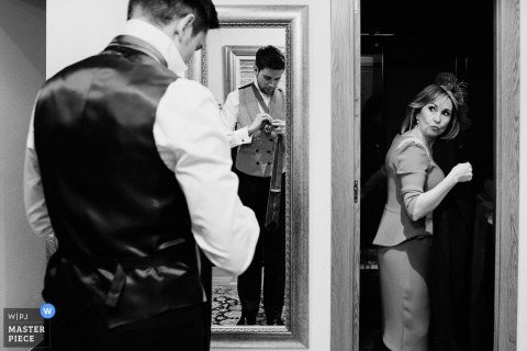 Black and white photo of a woman entering a room as the groom puts his tie on in front of a mirror by a Biscay wedding photographer.