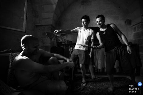 Schwarzweiss-Foto von zwei Männern, die den Bräutigam auflockern, während er von einem Lecce-Hochzeitsfotografen fertig wird.